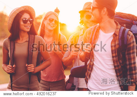 Hiking with friends is so fun. Group of young people with backpacks walking together by the road and looking happy