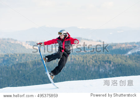 Male boarder jumping on his snowboard and taking his for the edge on top of a mountain against the backdrop of mountains  hills and forests in the distance. Carpathian mountains