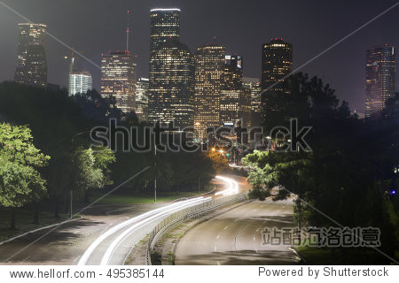 Long-exposure of cars racing over a freeway in downtown Houston  Texas with the Houston skyline in the background at night