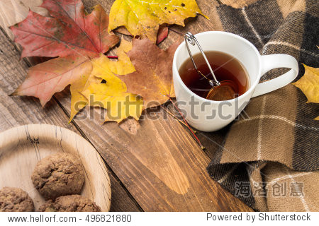 Cup of tea  homemade cookies  autumn maple leaves and woolen scarf on a wooden background.