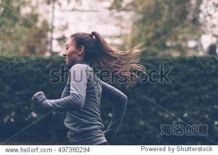 Woman running. Female runner jogging  training for marathon. Fit girl fitness athlete model exercising outdoor.