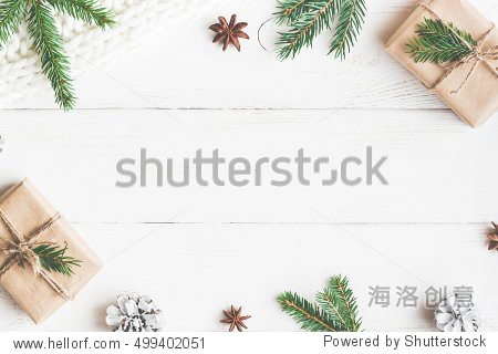 Christmas composition. Christmas gift  knitted blanket  pine cones  fir branches on wooden white background. Flat lay  top view  copy space