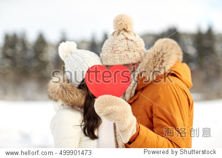 people  season  love  christmas and valentines day concept - happy couple hiding faces behind blank red heart over winter landscape