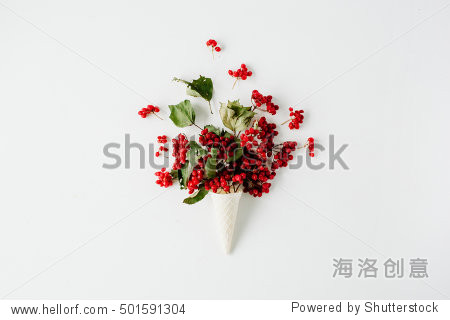 ice cream waffle cone with red rowan bouquet on white background  flat lay  top view. autumn wallpaper
