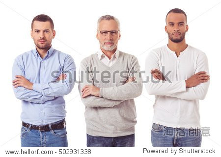 Three handsome businessmen in smart casual wear are looking at camera while standing with folded arms on a white background