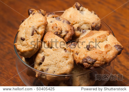 A heap of chocolate chip cookies against a wooden background