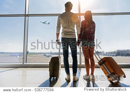 We are ready for new future. Young man and woman are watching flight at airport. They are standing and carrying luggage