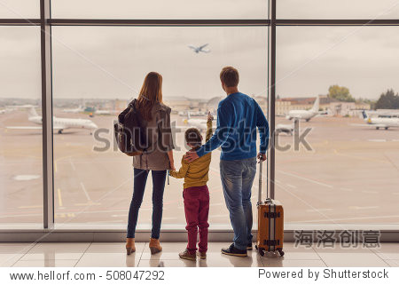 Such large aircraft. Back view shot of young family with luggage standing near window in airport before boarding