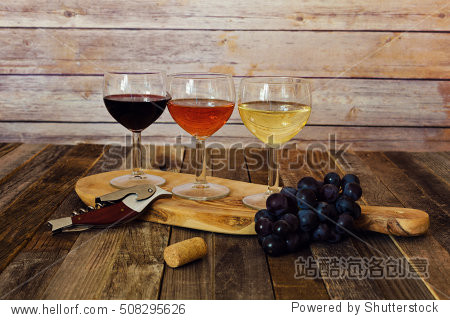 Wine flight on cutting board with grapes  cork and bottle opener