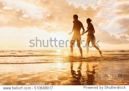 Happy cheerful couple having fun running to the sea together and doing splashes of water on a tropical beach at sunset - concept about romantic vacation  honeymoon