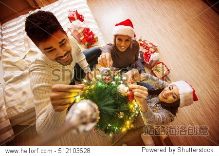 Preparations for holidays. Young friends decorating Christmas tree.