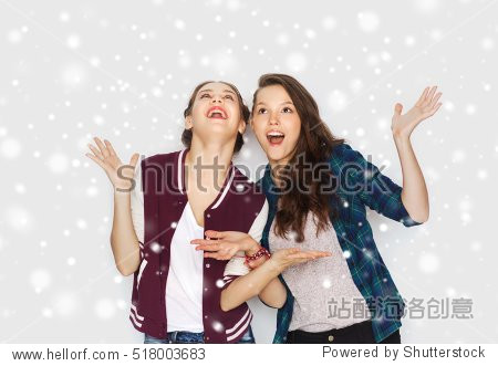winter  christmas  people and holidays concept - happy smiling pretty teenage girls or friends over gray background and snow