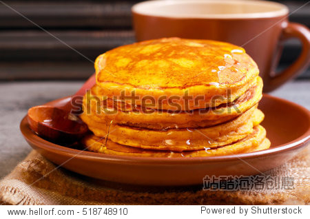 Pumpkin pancakes on plate with honey  on top