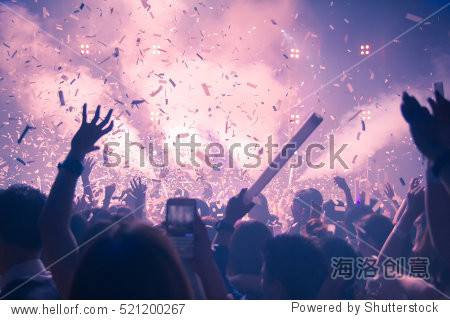 Silhouette hands of audience crowd people use smart phones enjoying the club party with concert.  Celebrate new year party   Blurry night club DJ party RCA Bangkok Thailand. Background Abstract.