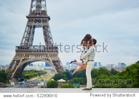 Loving couple having a date near the Eiffel tower. Romantic jump hug. Tourists on vacation or during their honeymoon in Paris  France