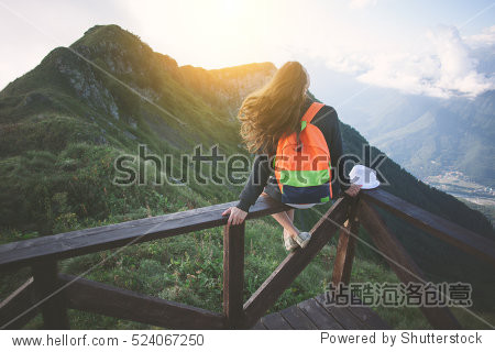 Young traveling woman with backpack sitting high on the top of the mountain with waving hair  evening with sunset