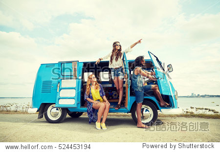 summer holidays  road trip  vacation  travel and people concept - smiling young hippie friends in minivan car on beach
