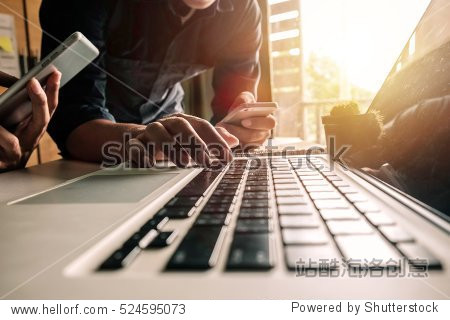 Businessman hand using laptop and tablet with social network diagram and two colleagues discussing data on desk as concept in morning light.