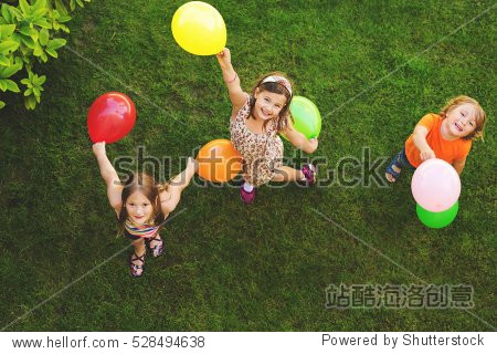 Three happy little kids playing with colorful balloons outdoors  top view
