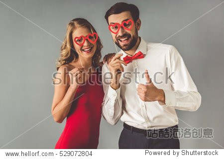 Beautiful elegant girl in red dress and guy in classic shirt and red bow tie are holding a paper heart glasses and smiling  on gray background
