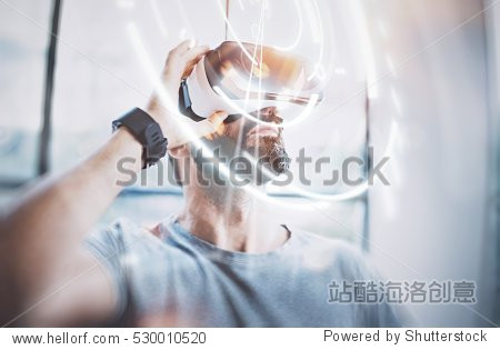 Concept of digital screen connection and interfaces.Attractive bearded man enjoyingvirtual reality glasses in modern loft studio.Smartphone using with VR goggles headset.Flare effect blurred