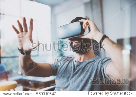 Young bearded man wearing virtual reality glasses in modern interior design coworking studio. Smartphone using with VR goggles headset. Horizontal,flares effect, blurred background