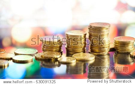 Golden euro coins stacks on bright light glowing bokeh background  business finance wealth and success concept