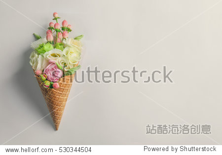 Waffle cone with composition of flowers and branches on white background