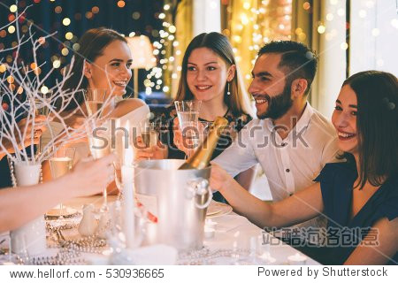 Friends celebrating Christmas or New Year eve. Party table with champagne. Toned picture