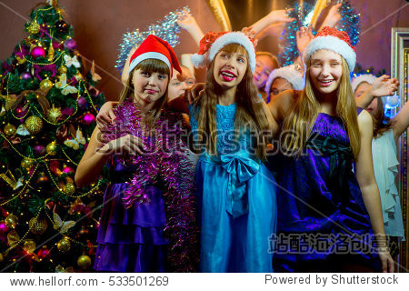 Group of cheerful young girls celebrating Christmas near the Christmas tree with lights