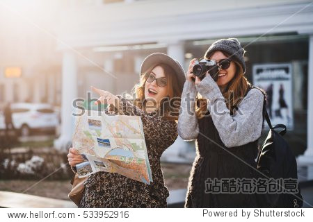 Happy travel together of two fashionable girls in sunny city centre. Young joyful women expressing positivity  using map  vacation with bags  camera  making photo  cheerful emotions  great mood