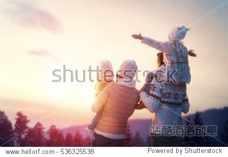 Happy family at sunset. Father  mother and two children daughters are having fun and playing on snowy winter walk in nature. The child sits on the shoulders of his father. Frost winter season.