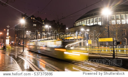 Long exposure shot in the city center of Manchester  UK with fast moving Metrolink tram in front of Manchester Central Library.
