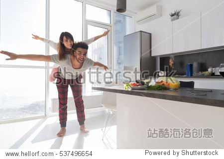Young Couple In Kitchen  Lovers Hispanic Man Carry Asian Woman Modern Apartment With Big Windows Interior