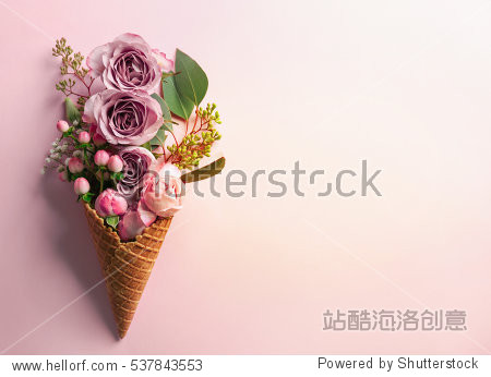 Waffle cone with composition of flowers and branches on pink background