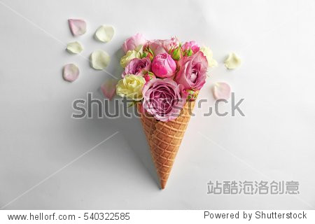 Waffle cone with bouquet of beautiful roses on white background