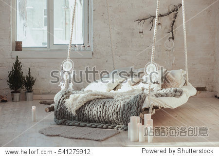 The bed suspended from the ceiling. Grey big cozy blanket knit. Scandinavian style  gray plaid  candles.