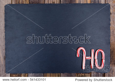 Holiday candy cane text HO on dark stone board and wooden background. Top view  flat lay.
