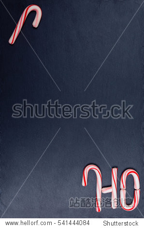 Holiday candy cane composition on dark stone board  background. Top view  flat lay.