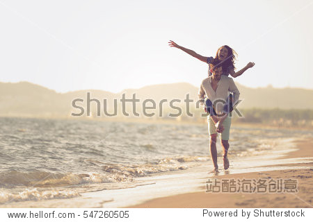 A guy carrying a girl on his back  at the beach  outdoors