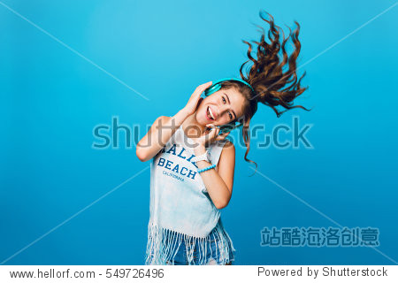 Energy girl with blue headphones  listening to music on blue background in studio. She wears white T-shirt  shorts. Long curly hair in tail is flying overhead from jump.