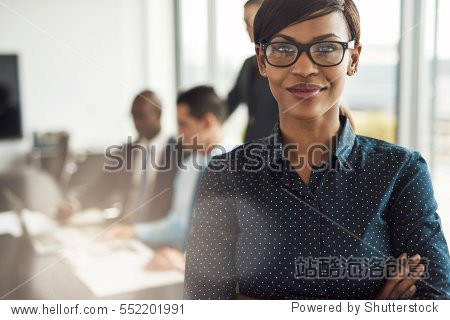 Beautiful young grinning professional Black woman in office with eyeglasses  folded arms and confident expression as other workers hold a meeting in background