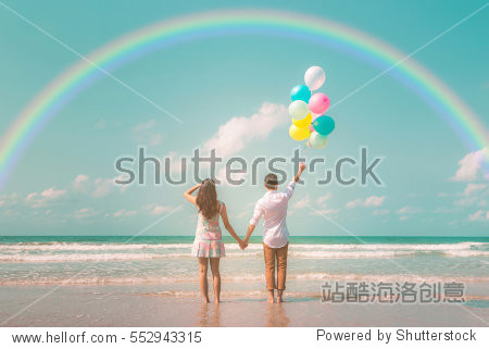 Portrait of couple of young happy married hipsters in trendy vintage clothes standing together on the beach with balloons and rainbow Pastel colors tone