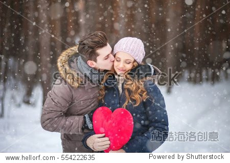 couple in the forest in winter  walk  kiss  hug and hold hands heart