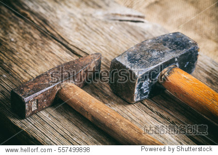 Two old hammers on a wooden table