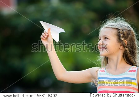 happy girl throwing simple paper airplane toy in air on sunny day