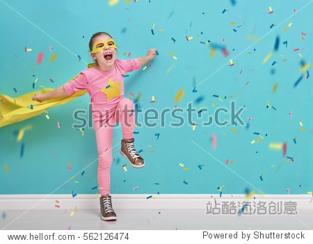 Little child plays superhero. Kid on the background of bright blue wall. Girl is throwing confetti and jumping. Yellow  pink and  turquoise colors.