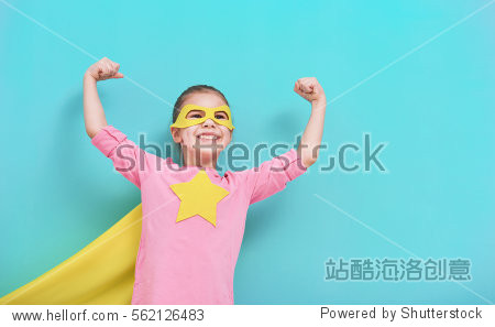 Little child plays superhero. Kid on the background of bright blue wall. Girl power concept. Yellow  pink and  turquoise colors.