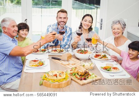 Portrait of smiling family toasting drinks at dining table