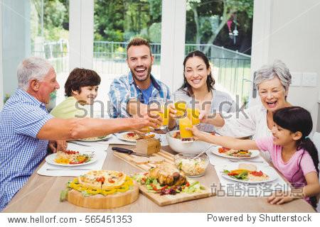 Smiling family toasting juice at dining table